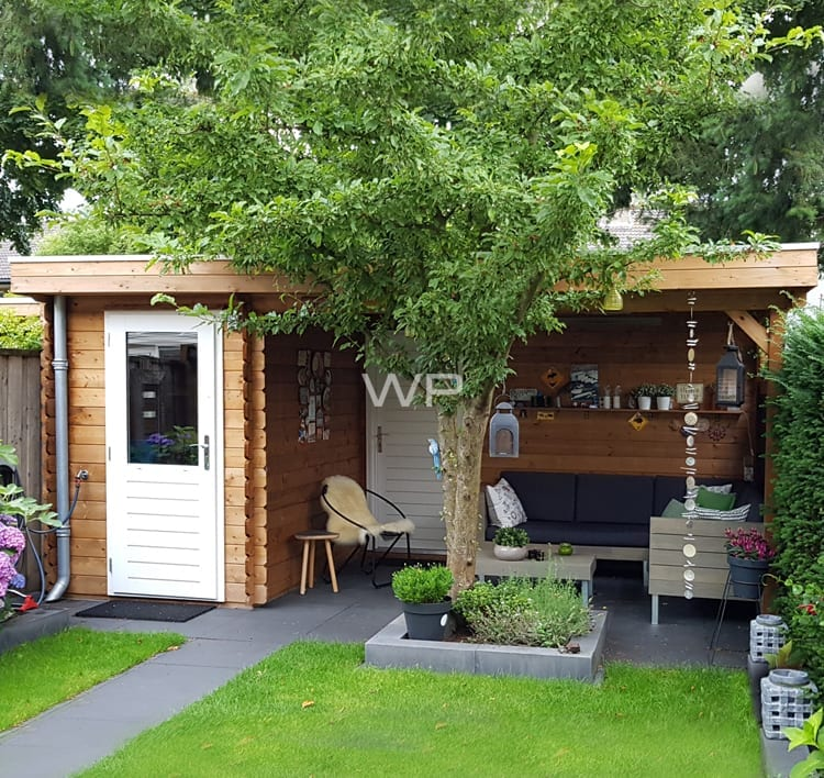 This small log cabin has a flat roof and a veranda
